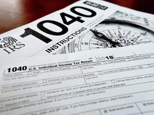 This Feb. 13, 2019, file photo shows multiple forms printed from the Internal Revenue Service web page that are used for 2018 U.S. federal tax returns in Zelienople, Pa. IRS data released Thursday, April 25, shows that while the average refund fell, the tax filing season was largely unchanged by the massive tax overhaul.