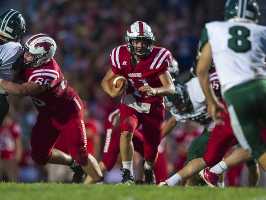 New Palestine High School junior Zach Neligh (11) scrambles