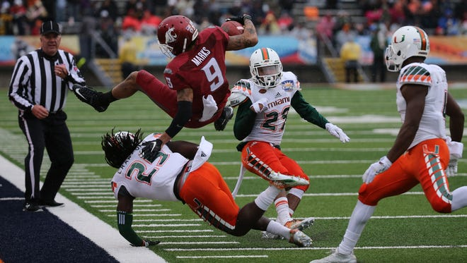 Washington State wide receiver Gabe Marks goes airbourne after being tackled by Miami Hurricanes defensive safety Dallas Crawford (25) during action in the Hyundai Sun Bowl.