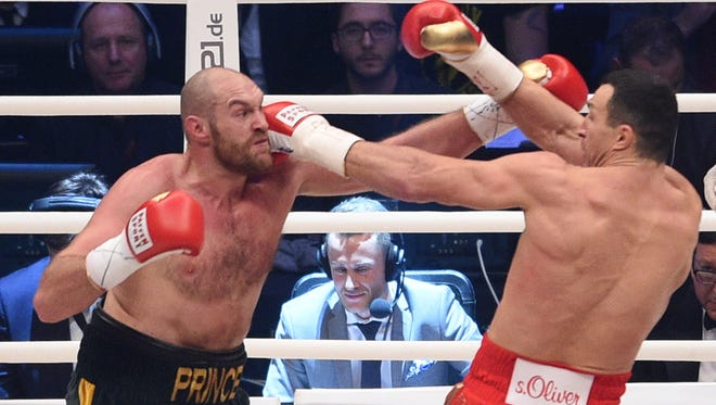FILE - In this Nov. 28, 2015 file picture Ukraine's Wladimir Klitschko, right, and Britain's Tyson Fury  compete  in a world heavyweight title fight for Klitschko's WBA, IBF, WBO and IBO belts in the Esprit Arena in Duesseldorf, western Germany.  The heavyweight rematch between Tyson Fury and Wladimir Klitschko has been rescheduled for Oct. 29 at the Manchester Arena. Fury beat Klitschko in November to claim the WBA, WBO and IBF titles. A rematch was originally scheduled for July 9 but was postponed after Fury sustained an ankle injury. The new date was announced Wednesday Sept. 7, 2016  by both fighters' management teams. (AP Photo/Sebastian Konopka,file)