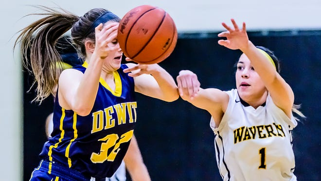 Maya Garrett ,1, of Waverly knocks the ball away from Jessah McManus of DeWitt.