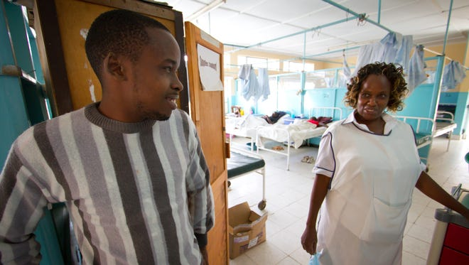 Pharmacist Douglas Osoro speaks with a nurse inside the men's ward of the Naivasha Sub-county Referral Hospital, where only a handful of patients remain months after doctors walked out on strike to protest Kenya's failure to implement a 2013 agreement that would have increased their pay and improved conditions in public hospitals. Jan. 30, 2016