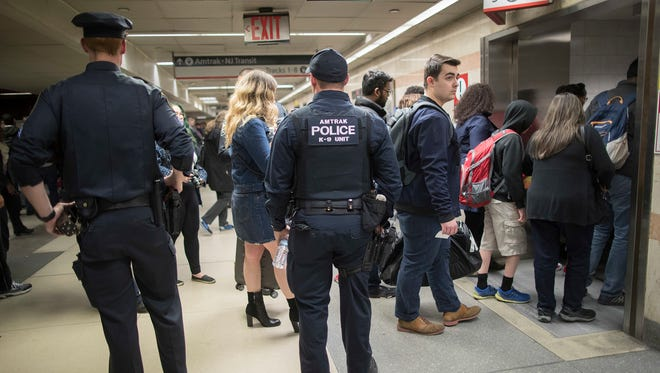 Amtrak police watch as passengers make their way to the track to board the first train to leave New York's Penn Station after delays caused by a stuck train, Friday, April 14, 2017, in New York. A New Jersey Transit train with about 1,200 passengers aboard was stuck in a Hudson River tunnel between New York and New Jersey. On Thursday, April 27, 2017, Amtrak announced plans for major repairs at the famous transit hub.