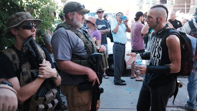 A Black Lives Matter supporter has a conversation and exchange of viewpoints with a man holding a rifle outside the Phoenix Convention Center before President Trump's speech Tuesday evening, Aug. 22, 2017.