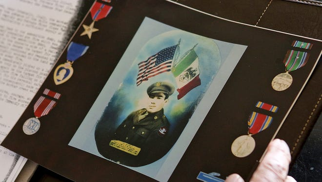 Roger Herrera looks over a photo of his oldest brother, Raul, and Raul's military honors Wednesday afternoon.