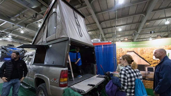 Visitors look over the Snap! Treehouse during the York RV Show at the York Expo Center Sunday. A hinge-form bed extends over the cab of the pickup truck, while side panels hinge open. The unit made in Newberry Township is made by Snap! Outfitters.