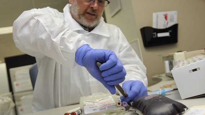 """An American Red Cross employee prepares donated blood for shipment at the Amercan Red Cross in Lansing in this 2012 photo. Red Cross confirmed last month a """"tentative decision"""" to limit the organization's operations in the region, eliminating 230 jobs - or 80% of its workforce - in its Great Lakes Blood Service Region, which includes Lansing."""