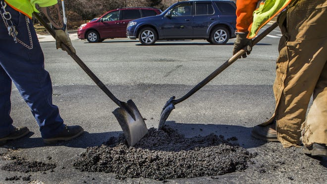 DelDOT crew members repair a pothole along Foulk Road near Brandywine High School.
