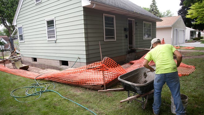 A basement repair crew from Andersen Basement Repair Inc. works to repair the foundation and basement walls of a house on Lark Street in Green Bay.