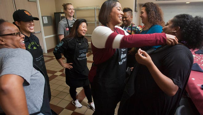 Surrounded by her bridal party, bride-to-be Marquita Thomas, center, helps her friends tie on aprons as they serve breakfast to guest families at the Ventura County Rescue Mission in Oxnard. The bridesmaids are, from left, Alonna Stevenson, Jessica Eglin, Heather Quinine, Stella Hwang, Shunte Wallace, Jenny Otineru and maid of honor Nichole Latimer. The women were serving the guests and set up a shop to provide the families with basic household items. The event was part of the bridal shower day for Thomas, who is getting married Oct. 21.