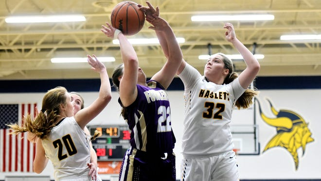 Haslett's Olivia Green, right, blocks a shot by Fowlerville's Jackie Jarvis, center, during the third quarter on Tuesday, Dec. 19 2017, at Haslett High School. Green's teammate Taylor Rahl, left, looks on. Haslett won 51-49.