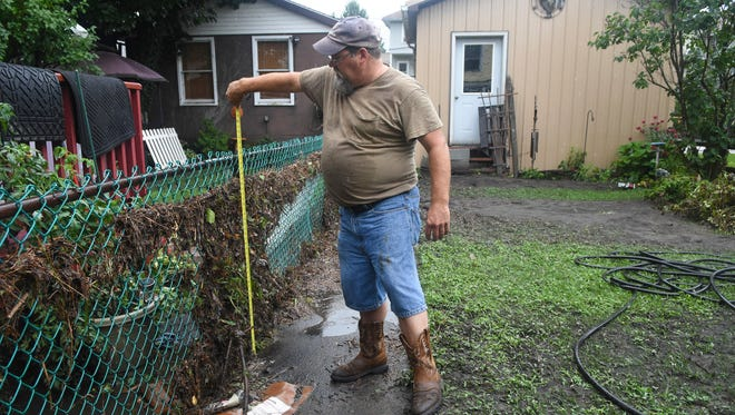 Daniel Noll Sr. measures how high the flood water reached in his backyard on Spring Street during an interview in Tremont, Pa. on Tuesday, July 24, 2018.