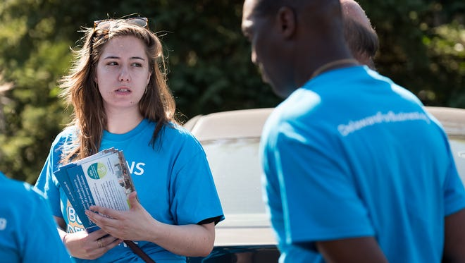 Julijana Englander, of Tusk Strategies, helps organize members of Citizens for Pro-Business Delaware, a group made up of TransPerfect workers, before they canvas neighborhoods in Wilmington on Wednesday.