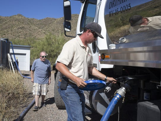 Damon Bruns (right) of Dynamite Water turns off the
