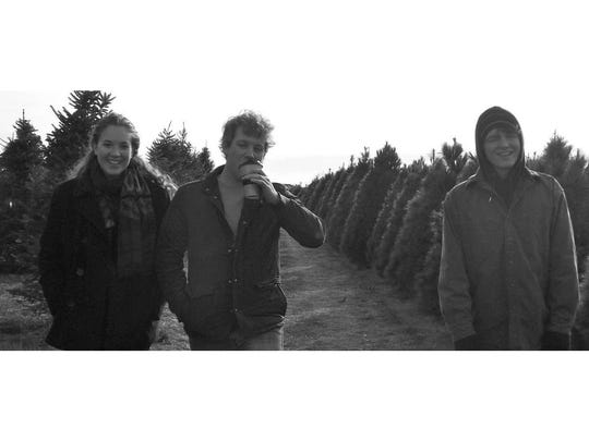 Emma, Max and Ben Wellman help pick a tree in Cumming.