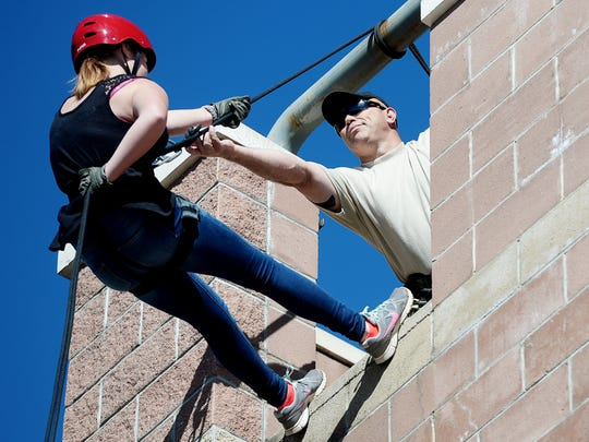 First Sergeant Chad Prevatte reaches out to Kayla Clubb, an Erwin JROTC student, as she prepares to rappel at Swannanoa Fire Department October 18, 2017.