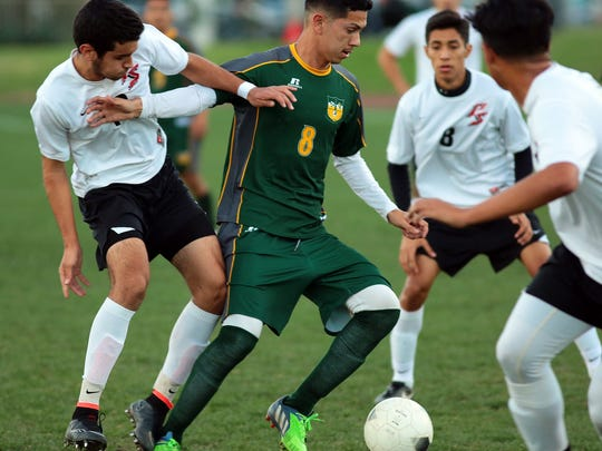 Coachella Valley senior Oscar Aguirre (8, green) works the ball through a gaggle of Palm Springs Indians while playing on the road Wednesday night, February 11, 2015. Coachella Valley had a 2-1 lead at the half.