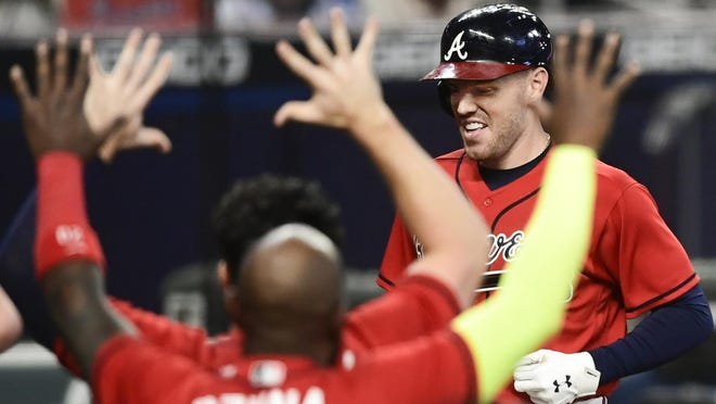 Atlanta Braves' Freddie Freeman crosses home plate to score on a winning two-run home during the 11th inning Fridy night against the Boston Red Sox in Atlanta.