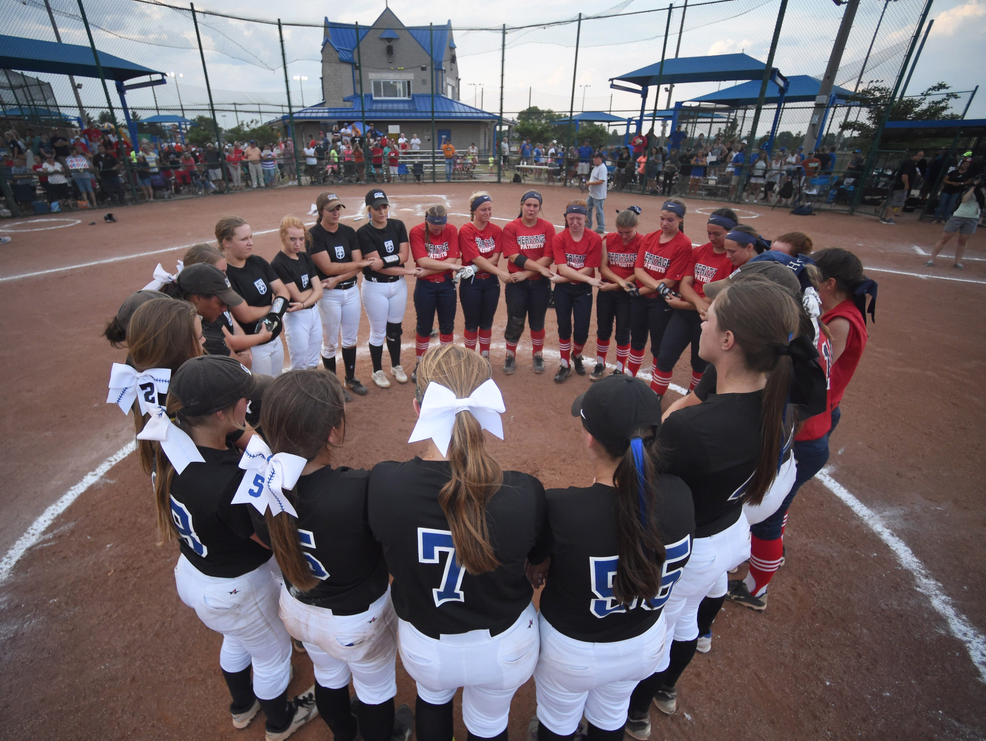 CAK and White House Heritage players pray together in a circle after CAK's 4-0 victory in a Class AA state championship softball game at StarPlex Park in Murfreesboro during Spring Fling on Friday, May 27, 2016.