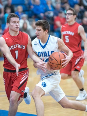 Wynford guard Josh Crall's drive to the basket is disrupted by Bucyrus' Gram Dick.