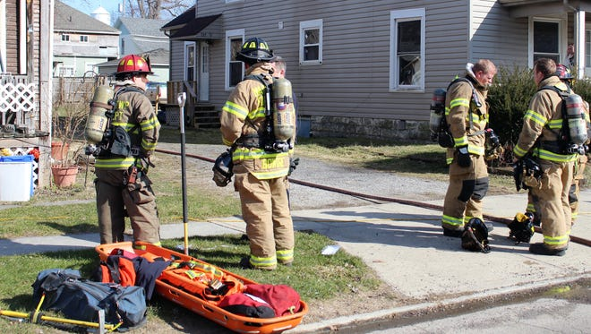 Marion City firefighters inspect a house on Pearl Street after the kitchen area caught on fire.