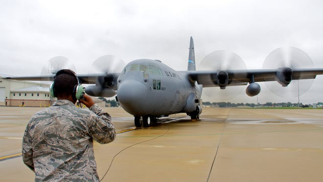 An airman keeps in contact with fellow maintainers as engines run on a C-130H at the Delaware Air National Guard Base.