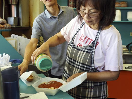 In this Thursday, March 14, 2019 photo, Belinda Lau, manager of the Wiki Wiki Drive Inn takeout restaurant in Honolulu, sprinkles cheese on an order of spaghetti in a styrofoam container.