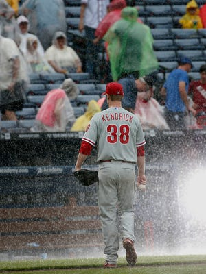 Phillies starting pitcher Kyle Kendrick leaves the field as play is stopped for rain during the sixth inning of the Phillies' 8-2 loss to the Braves Sunday..