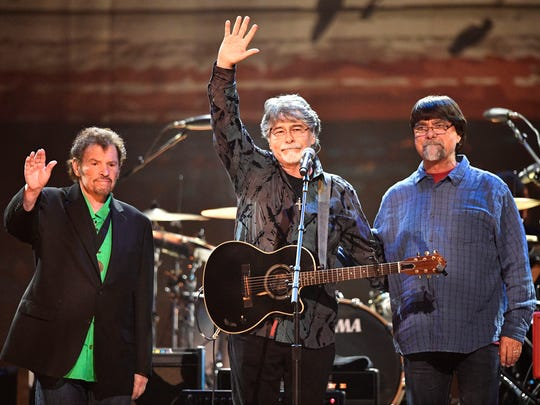 From left, Jeff Cook, Randy Owen and Teddy Gentry, of country music group Alabama, wave to the crowd at the Merle Haggard Tribute concert on April 6, 2017, in Nashville.