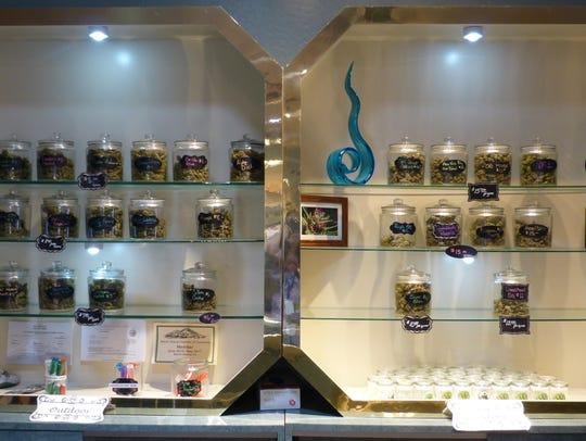 Jarred marijuana strains sit on display behind the