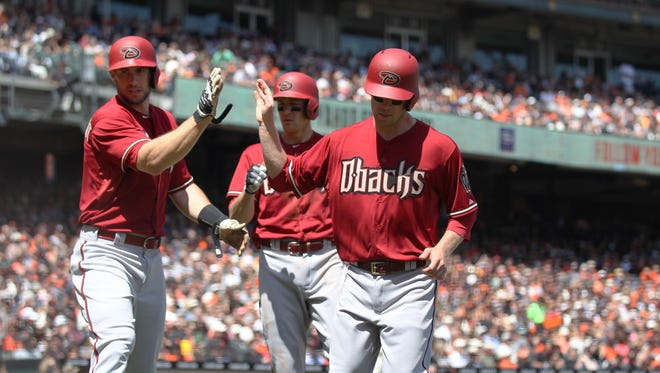 Apr 19, 2015: Arizona Diamondbacks third baseman Aaron Hill (2) high fives first baseman Paul Goldschmidt (44) after they both score on a two run single against the San Francisco Giants as on deck hitter Nick Ahmed (back) looks on during the third inning  at AT&T Park.