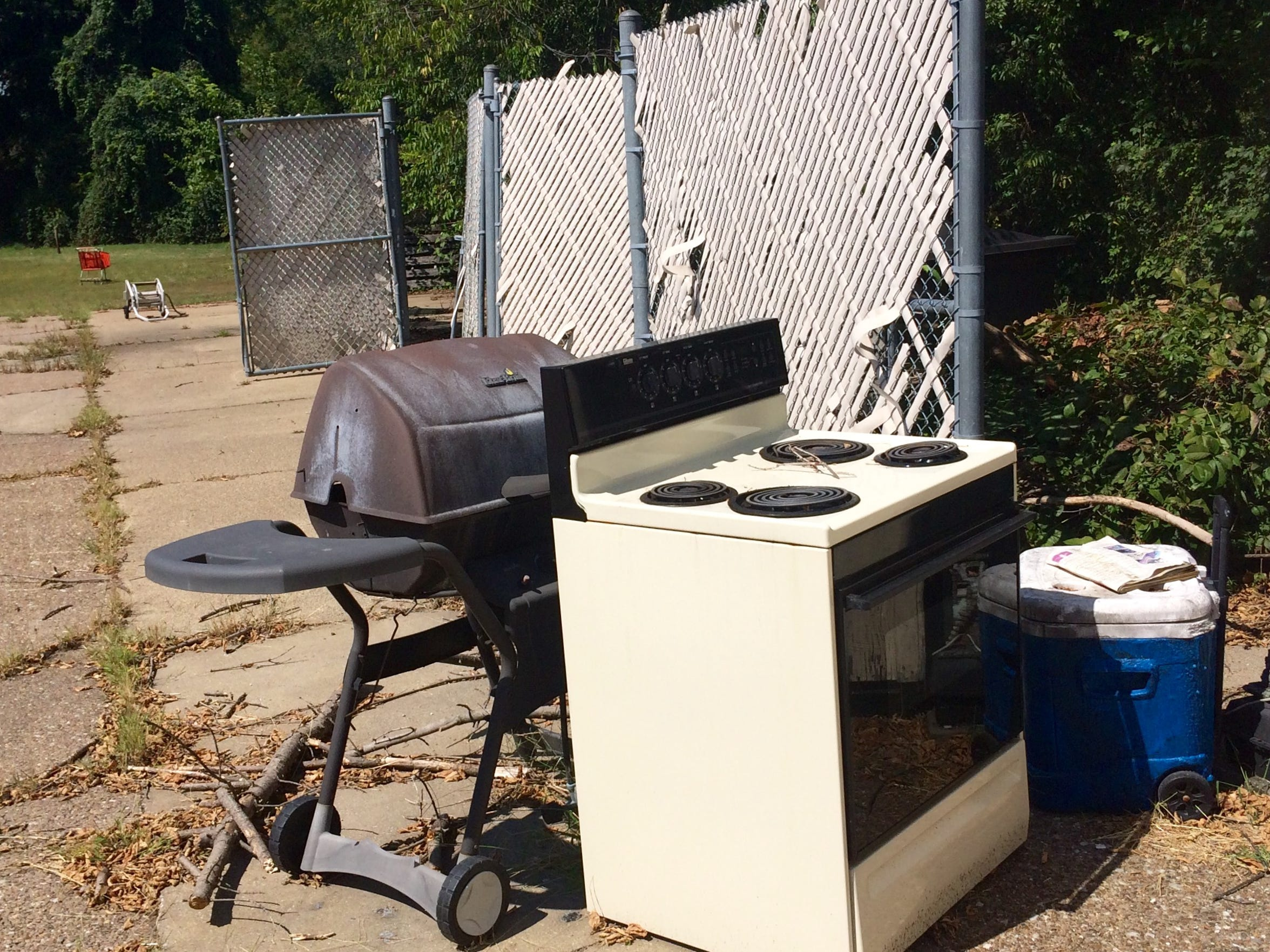 A discarded grill and home oven in the rear of the