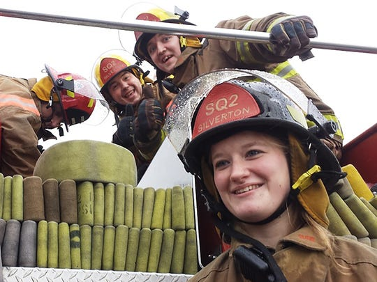 Probationary Firefighters Paul Scoville, Noah Clemmons and Kylee Vodden take a break while Lt. Ray Dandeneau still inspects a re-load of equipment.