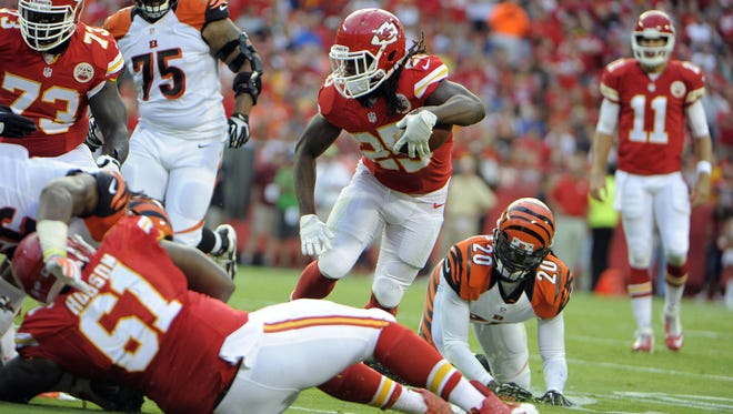 Kansas City Chiefs running back Jamaal Charles (25) escapes the tackle of Cincinnati Bengals free safety Reggie Nelson (20) in the first half at Arrowhead Stadium.