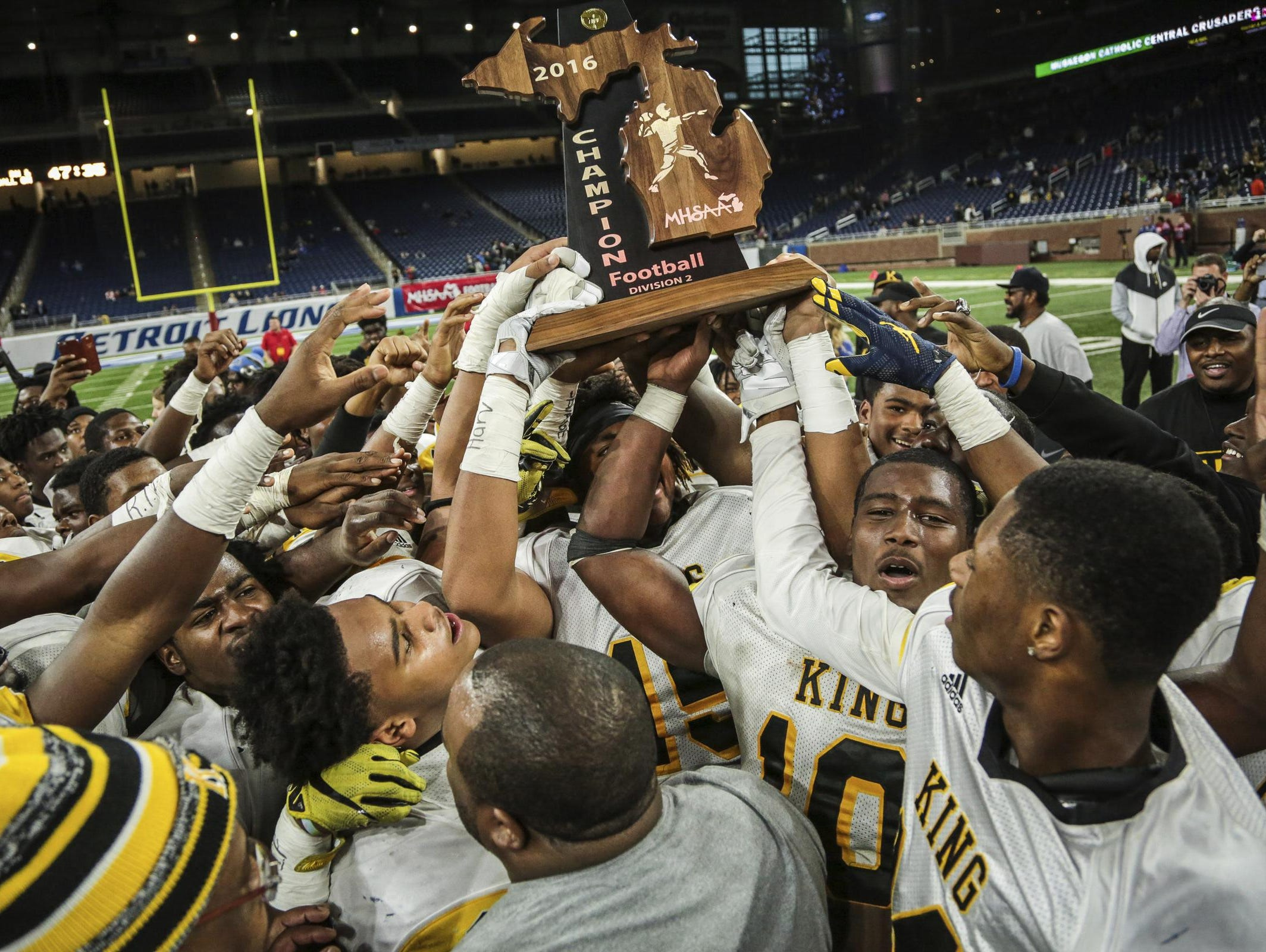 Detroit King players celebrate winning the title against Walled Lake Western during the Division 2 title game Friday.
