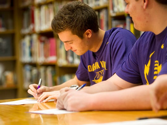 Regina's Jacob Adam signs an institutional letter of intent to UNI at Regina on Wednesday, Feb. 4, 2015.