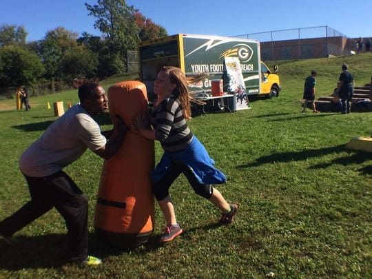 """Johnathan Franklin, who played with the Green Bay Packers last season, blocks a student during """"Fuel Up to Play 60"""" activities Tuesday at Howe School."""