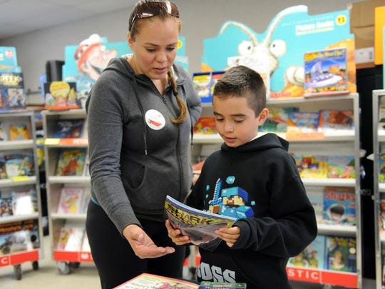 "At the Boronda Meadows Elementary School Book Fair in Salinas, Leonardo Lopez, 7, ponders ""Shark Attack"" as his mother Yesi looks on."