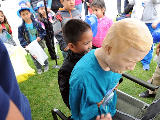 "A student from Jesse B. Sanchez Elementary School tries the Heimlich maneuver on ""Choking Charlie"" at Wednesday's annual Emergency Medical Services Week event in Salinas."