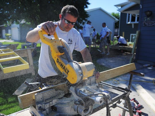 Justin Driscoll, a volunteer from Driscoll Construction, cuts a piece of lumber while working on a deck with a ramp at Ron and Onalea Barber's home during the Home Builders Association of the Sioux Empire's 22nd annual Repair Affair Day on Tuesday, June 9, 2015, in Sioux Falls. More than 60 volunteers made repairs to six different homes Tuesday throughout Sioux Falls.