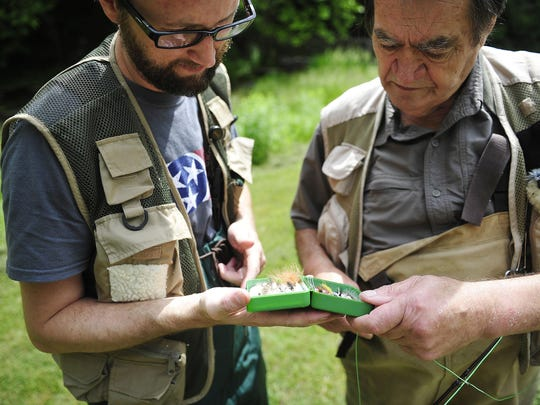 Trey Cioccia, founder and executive chef of The Farm House Restaurant, and trout farmer Bob Lukens look for a fly to fly fish at Bob White Springs trout farm in Only, Tenn. Lukens sells fish to Cioccia at his restaurant.