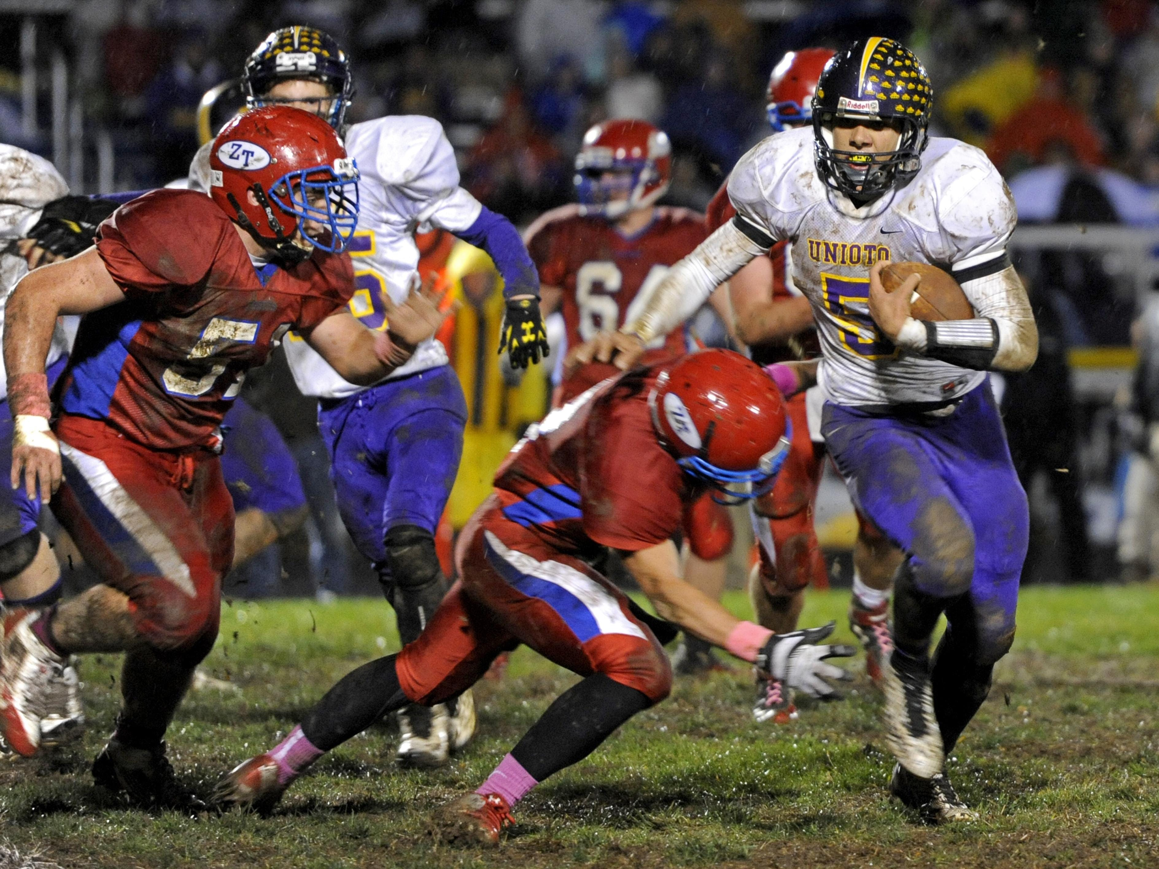 Erique Hosley carries the ball against Zane Trace during the 2014 season. Hosley and his teammates will be under the direction of new head football coach Jeff Metzler in 2015.