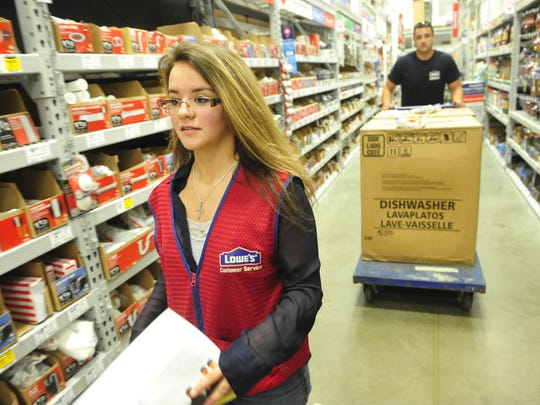 Sabrina Marcum walks down an aisle to find a water hose that fits subcontractor Caleb Herndon's dishwashers at Lowe's in Gallatin, Tenn., on Friday, July 17, 2015.