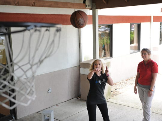 Tara Kuzma, physical therapist with Genesis COOR, looks on as Stephanie Latier shoots a basket during a therapy session. Stephanie was captain of her high school soccer team at John Glenn High School and actively participated in athletics until her crash in February. Regaining those athletic abilities is a long-term goal for her.