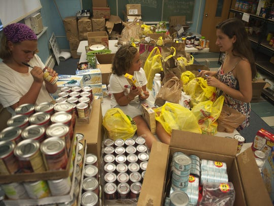From left, Moorestown's Grace Buss, Abigail Buss and Alexis Angelini work at their food pantry for their nonprofit Live Civilly. They started the nonprofit about six years ago to help fight hunger and it has blossomed into so much more.
