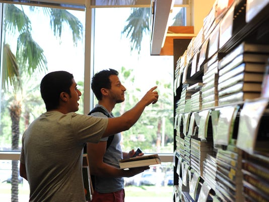 University of Tampa students Khalid Alrashed, left, and Ammar Bashawri, compare book prices at the Vaughn Center on Tuesday, Aug. 27, 2013 in Tampa, Fla. Some local bookstores said students still prefer print textbooks over electronic versions.