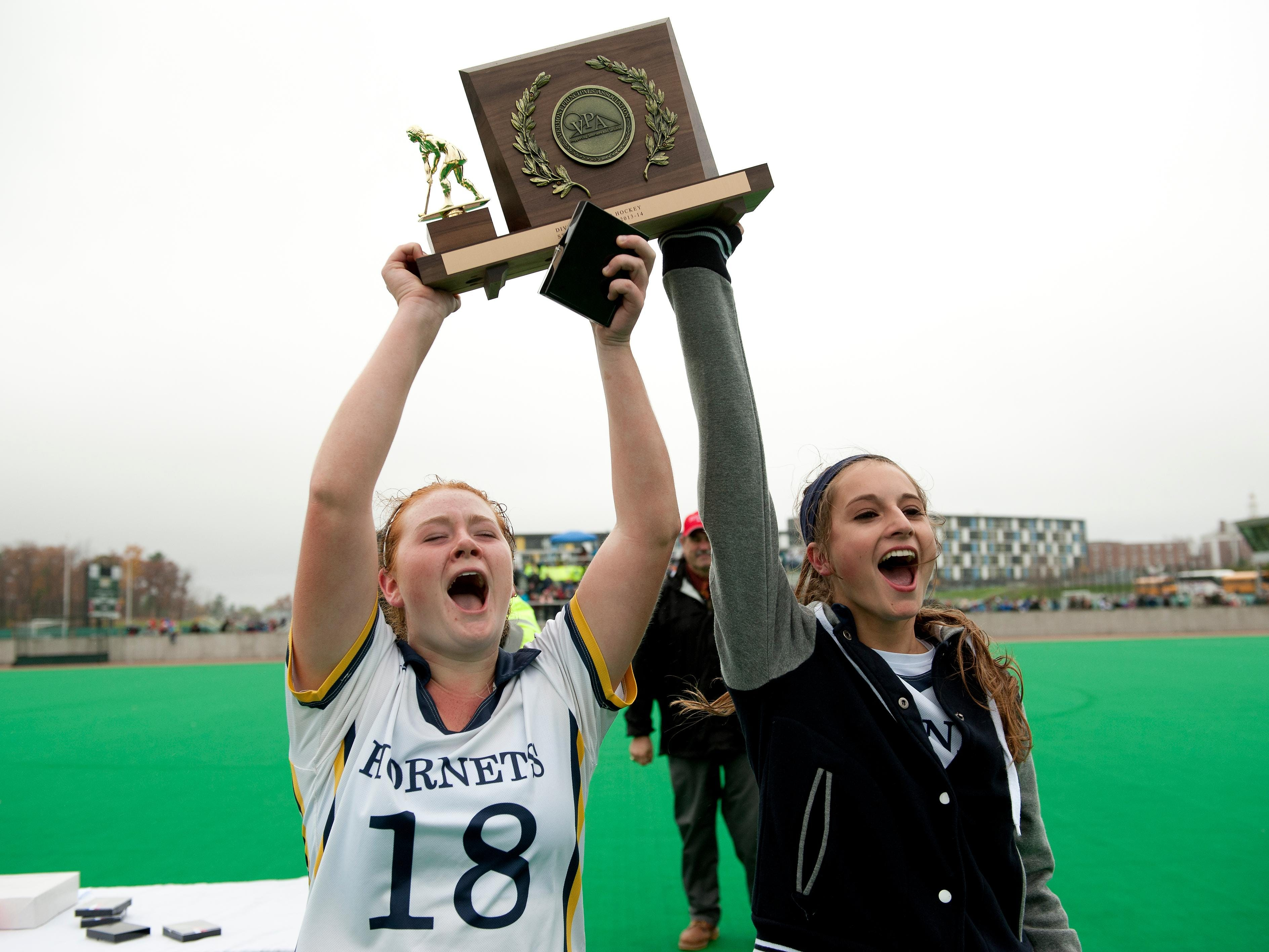 Essex captains Paula Noordewier, right, and Alexandra Celia hold up the trophy awarded to the Division I field hockey state champions by the Vermont Principals' Association on Nov. 2, 2013.