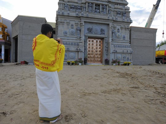 Sai Prem of Ann Arbor takes a photo of the tower during the the grand opening of the Rajagopuram at the Parashakthi Temple in Pontiac.