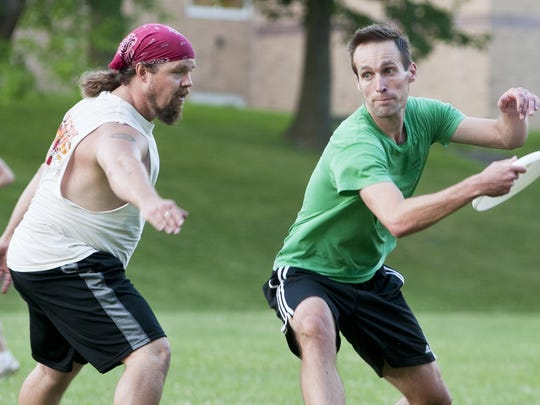Sheboygan Ultimate's Joe Hullin, right, makes a pass to his teammate while Manitowoc Ultimate Frisbee Concern's Joe Martinson defends during a match in the bowl of Wilson Junior High School on Wednesday, Aug. 12, in Manitowoc. About 30 participants came out to play the match.