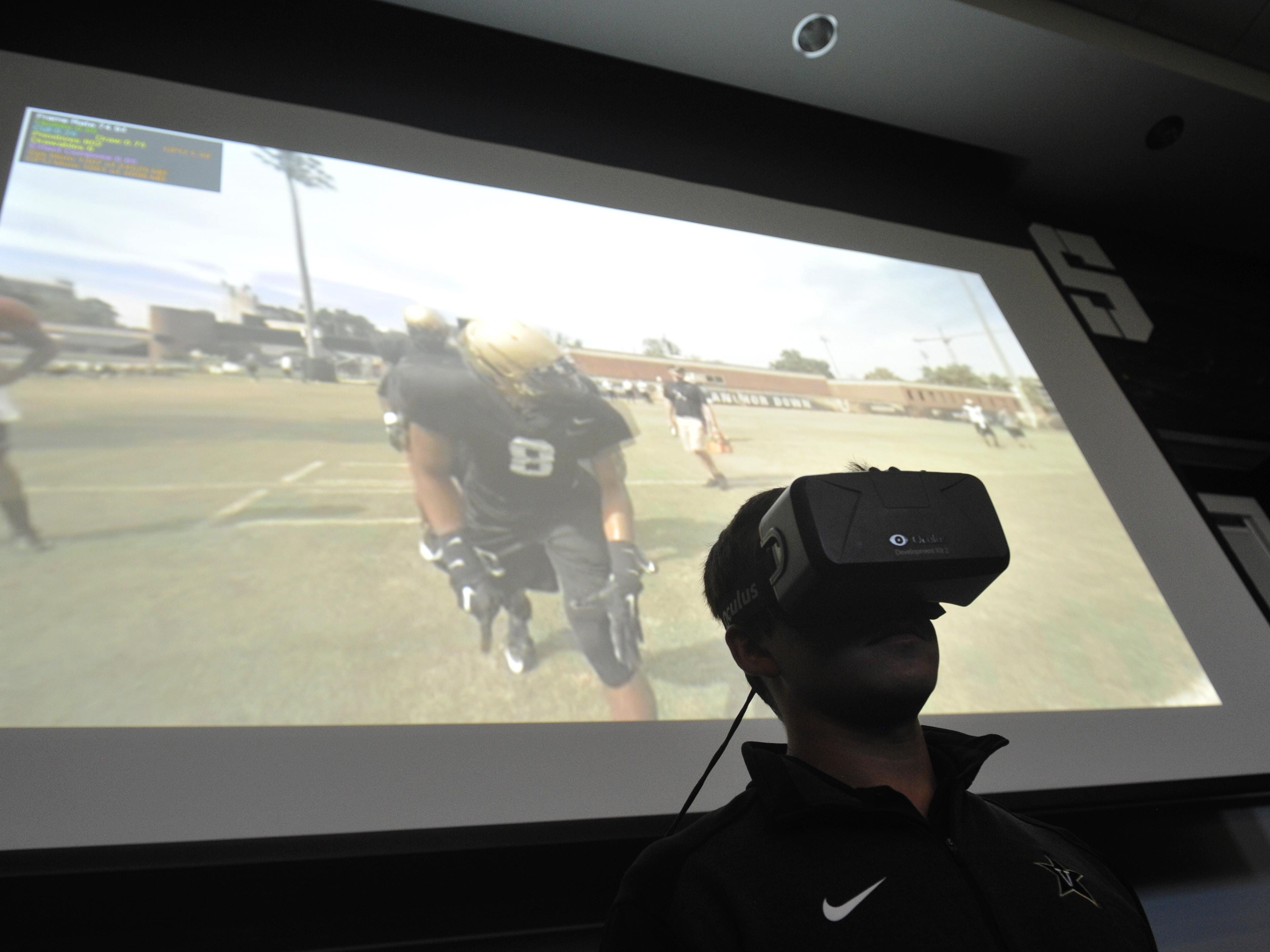 Josh Pohl, Vanderbilt's assistant director of video productions, demonstrates the virtual reality gear in the team meeting room. Video is taken with a 360-degree cluster of cameras mounted on a light-weight tripod and then viewed through a headset or on a screen.